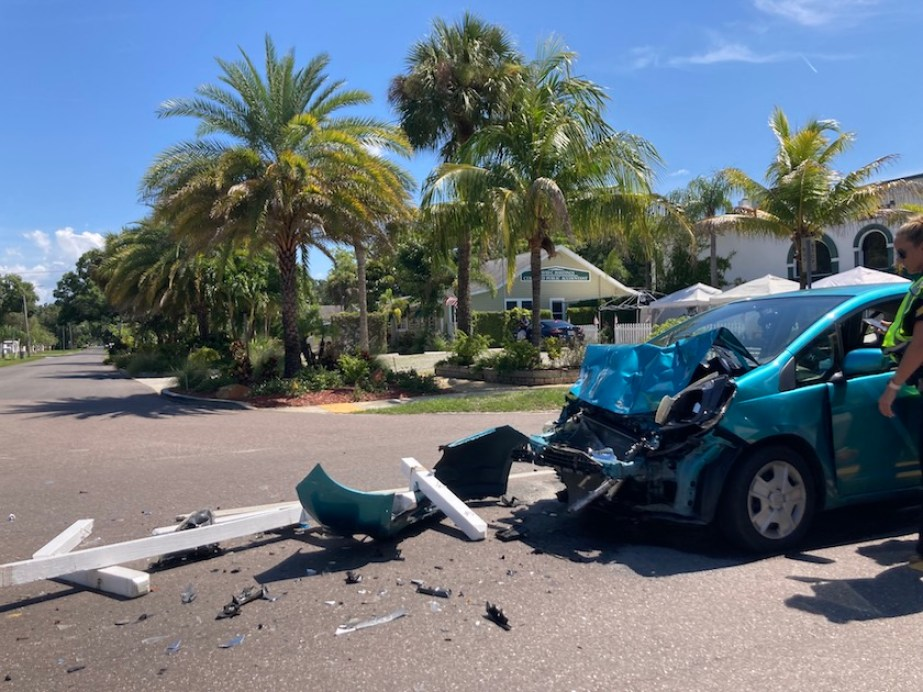A photo of white posts scattered on a roadway with a blue car damaged in an accident, blue sky and palm trees
