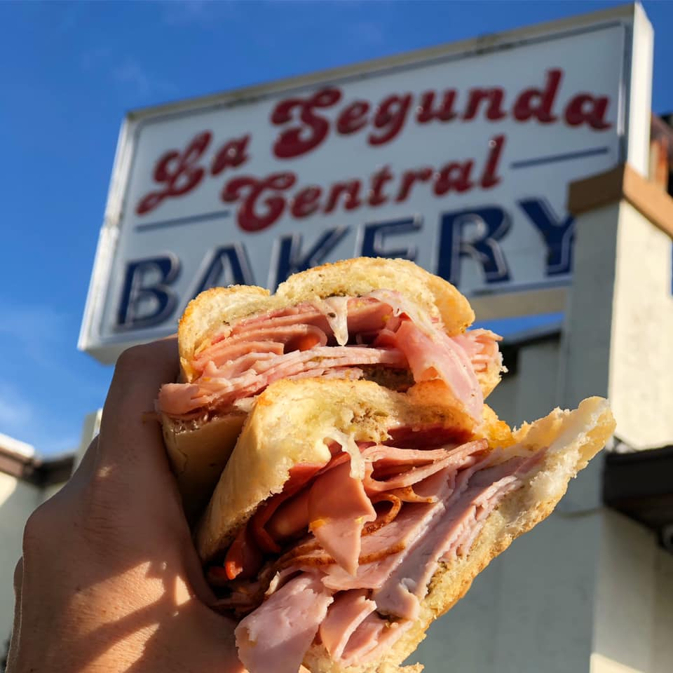"""A photo of a sandwich in front of a sign that reads """"La Segunda Central Bakery"""""""