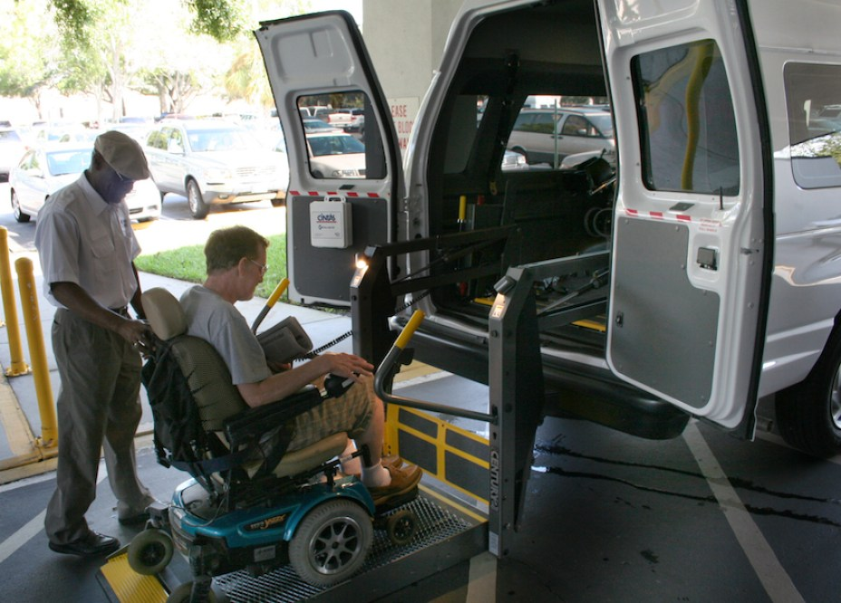 A man assisting a disabled man in awheelchari in the back of a large white van.