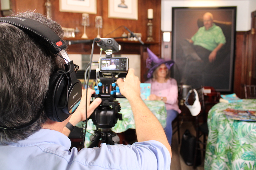 A photo of the back of a man operating a camera filming a woman in the background in a pink top and purple witches hat next to a large portrait of a man.