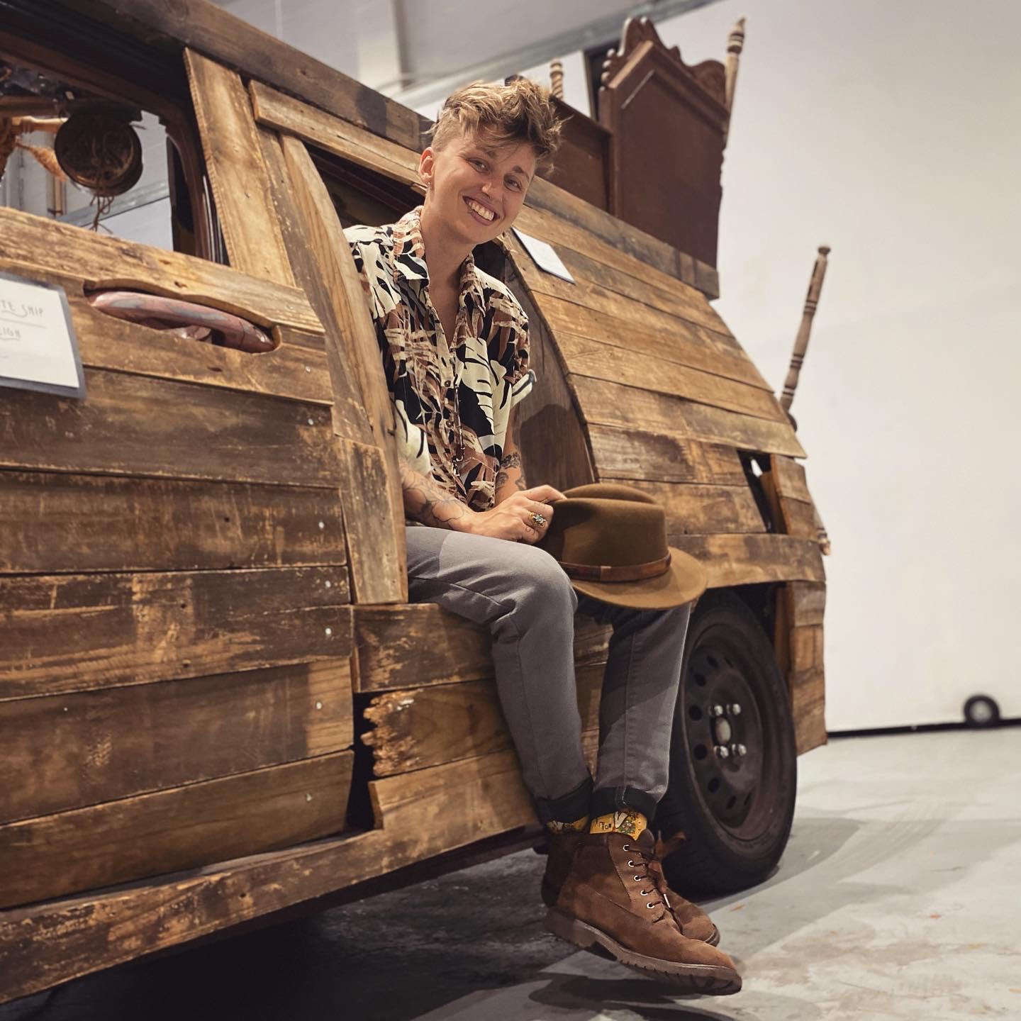 A photo of a person sitting in the wooden facade of a pirate ship/car mobile smiling at the camera.
