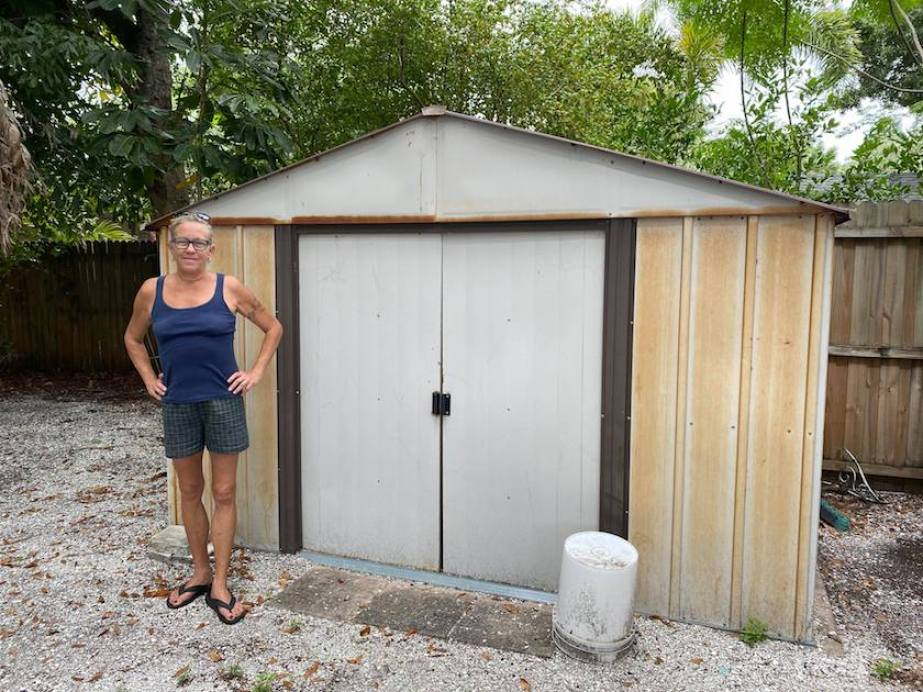 A woman in a tank top and shorts standing next to a white and brown shed.