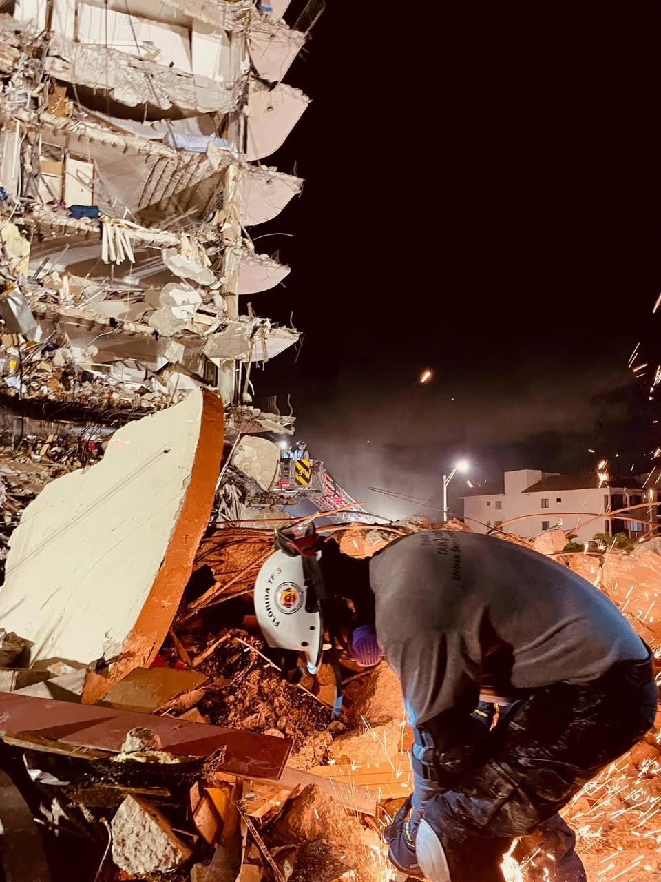 A photo of a rescue worker in the rubble of a collapsed building at night.