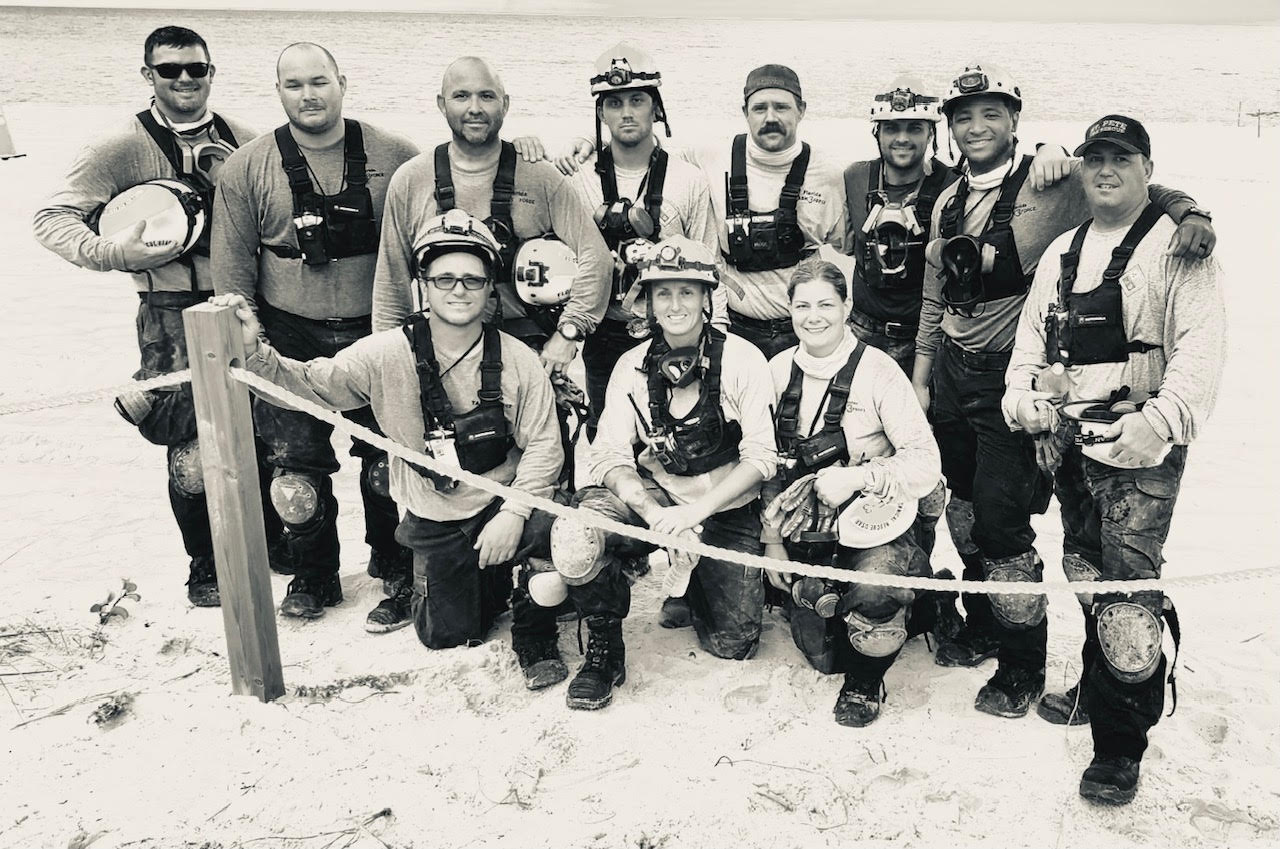 A group photo of first responders in emergency gear in black and white.