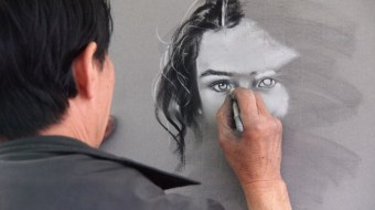 Man with black hair drawing a black and white woman