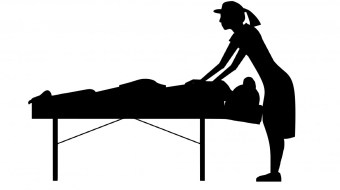 Clip art black shadow of a woman in a hat massaging a person on a massage table