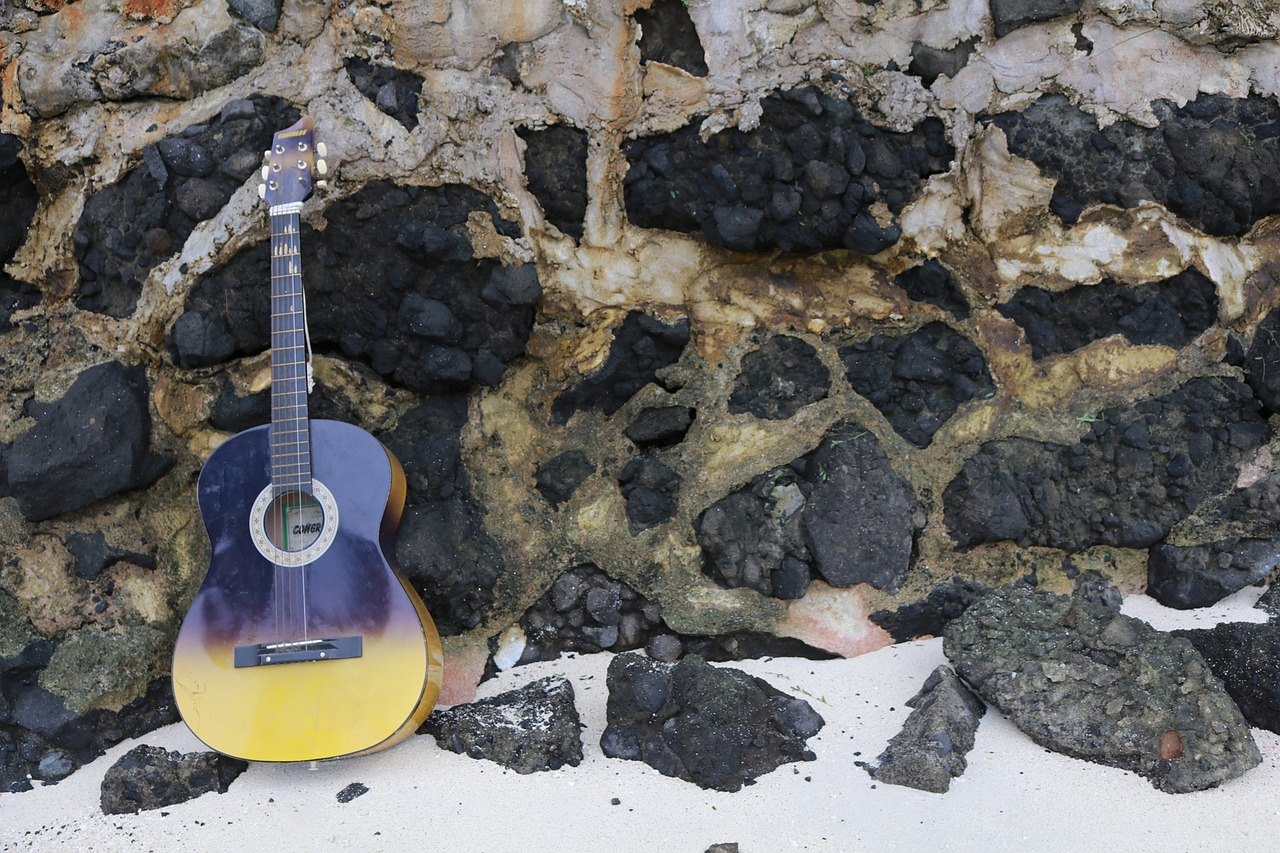A brown and yellow guitar propped up on some rocks in the sand.