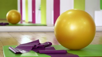 Yellow exercise ball on green workout mat