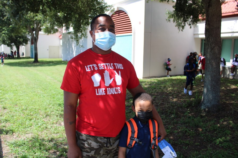 A man in a red shirt and face mask stands outside with a little boy in a backpack and a face mask.