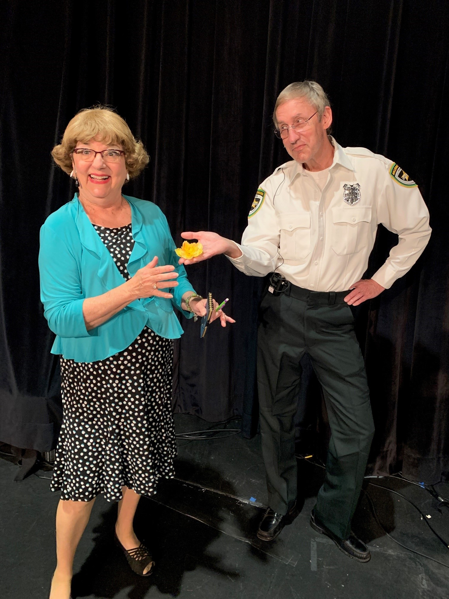 A photo of an older man and woman on a stage acting in character.