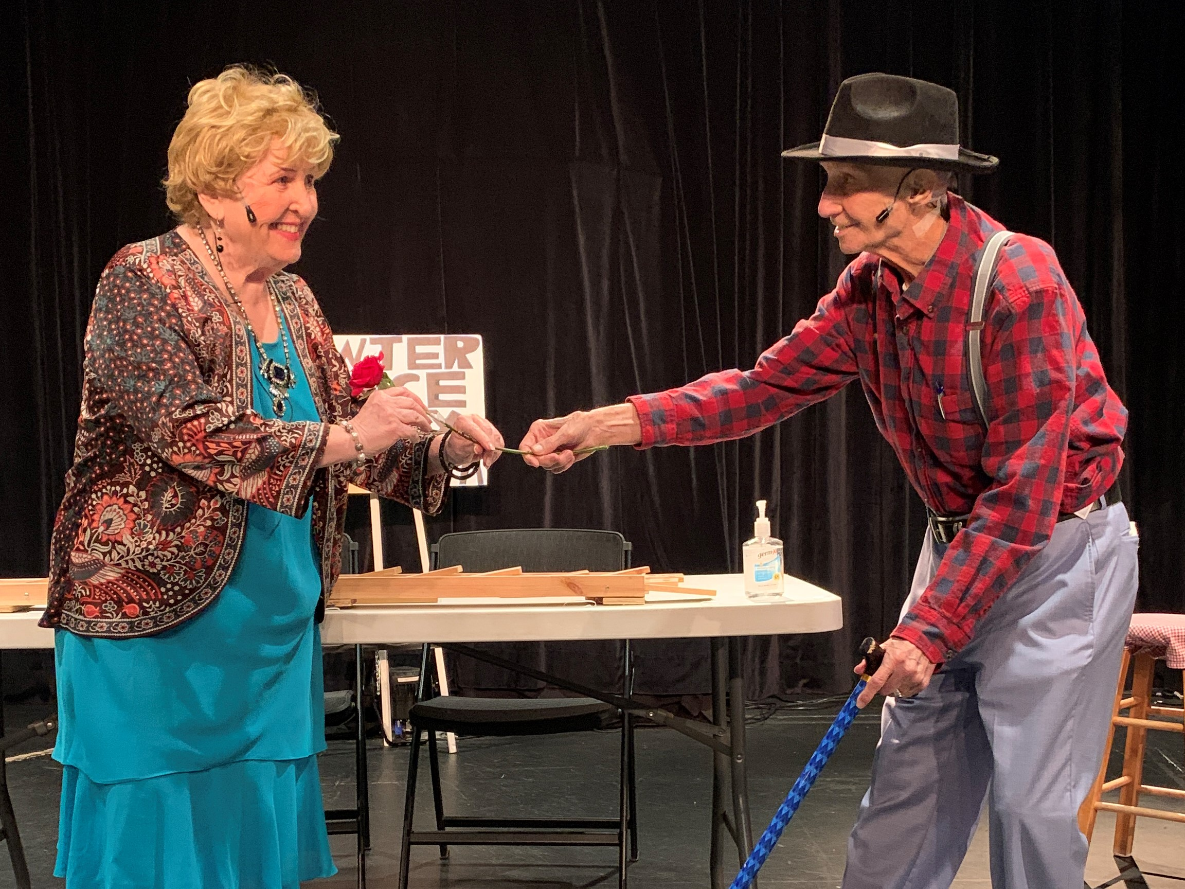 A photo of an older man and woman on a stage acting in character at a prop table.