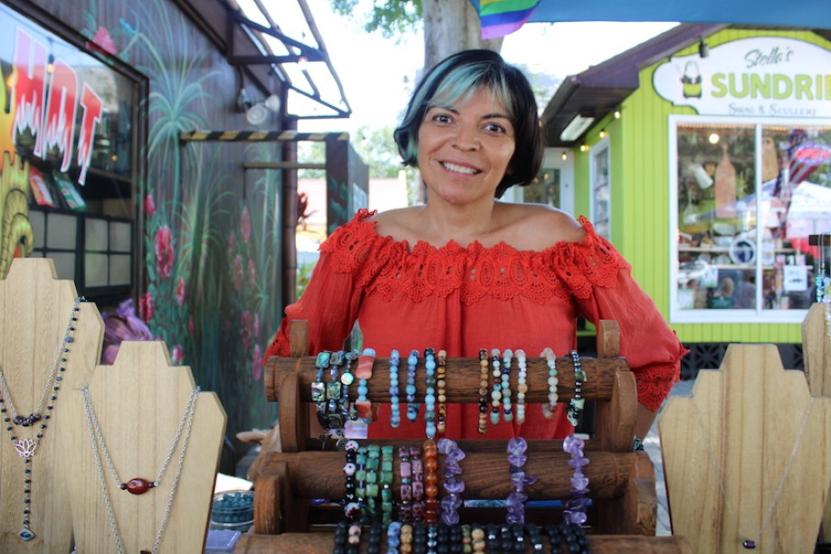 A woman in a red shirt at an outdoor jewelry stall smiling at the camera.