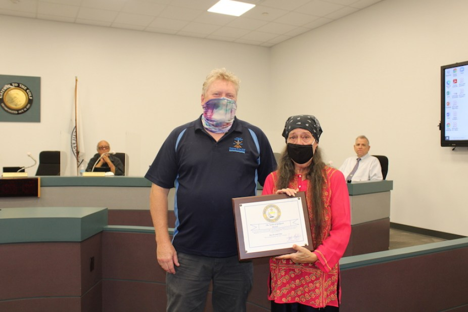 A man and a woman in face masks indoors pose for a photo with a plaque.