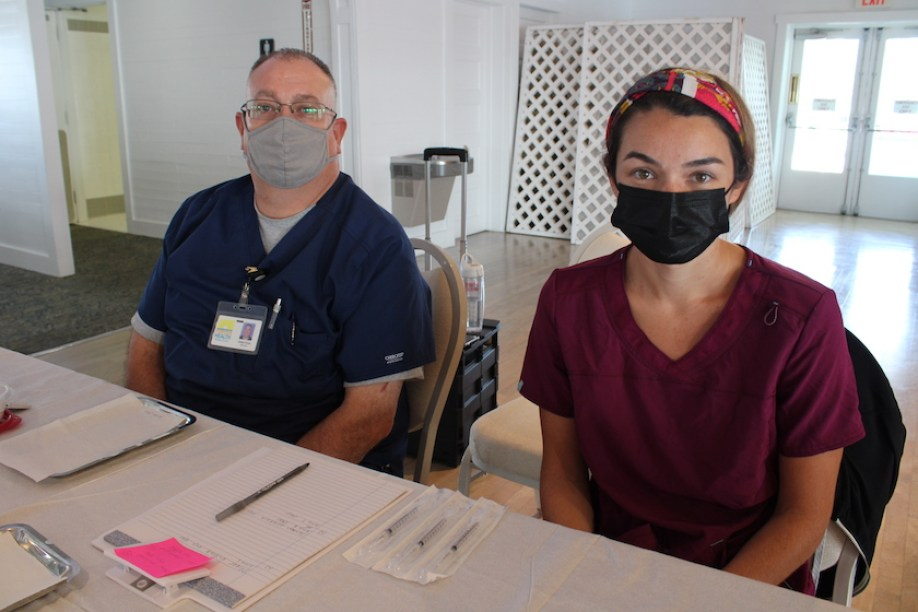 A photo of a man and a woman in scrubs in facemasks sitting at a table looking at the camera.