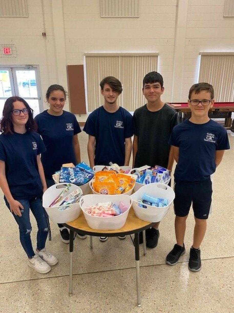 A group of five teens in blue uniform shirts standing around a table of toiletries in bins.