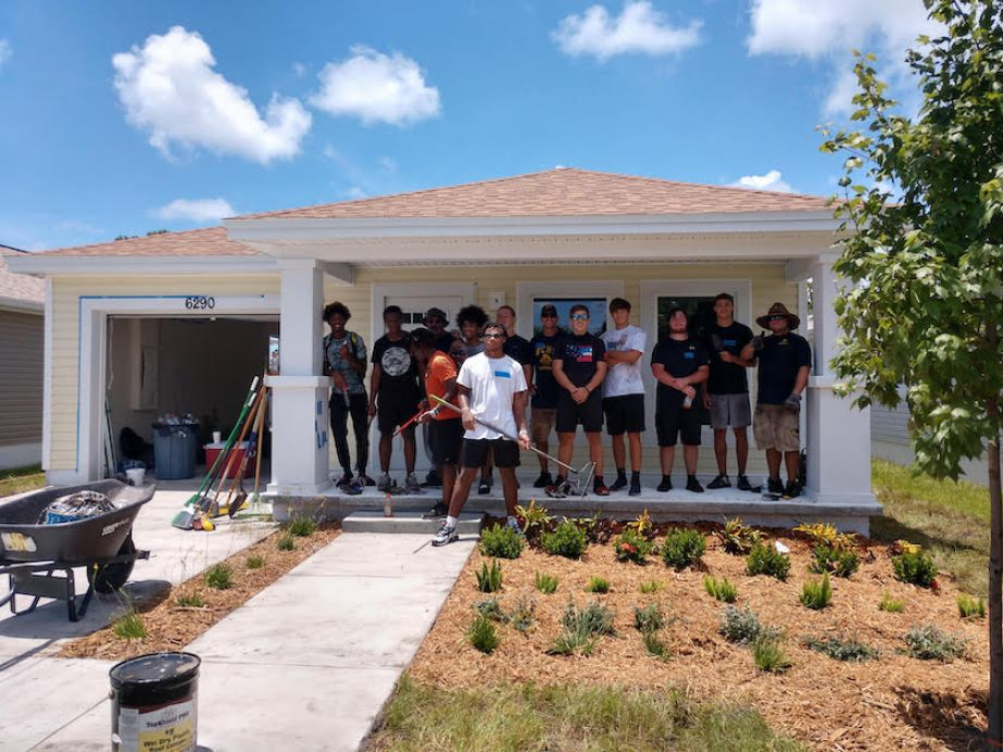 A photo of a group of teenagers posted in front of a house with new landscaping.