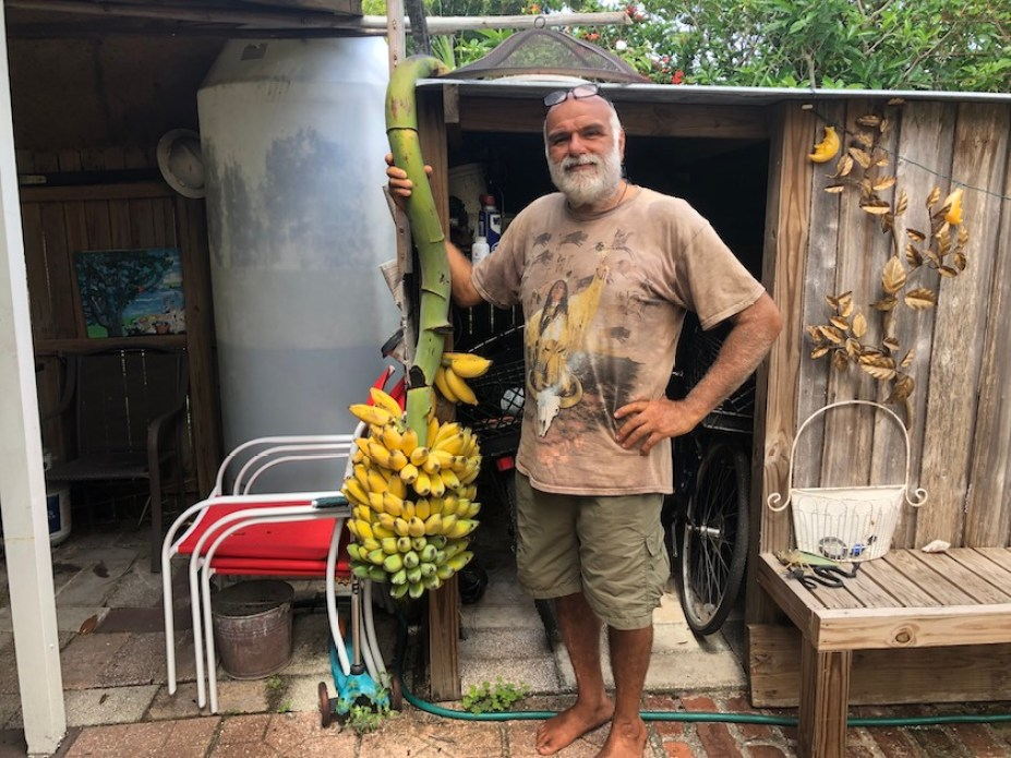 A man with a beard standing outside holding a large bunch of bananas.