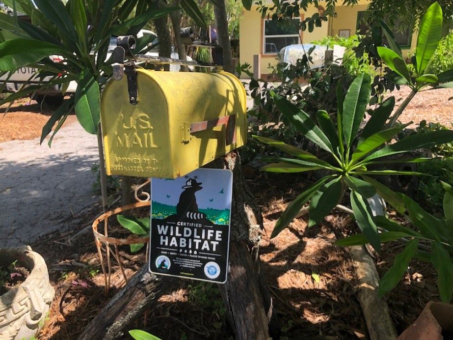 """A yellow mailbox with a sign that reads """"wildlife habitat"""""""