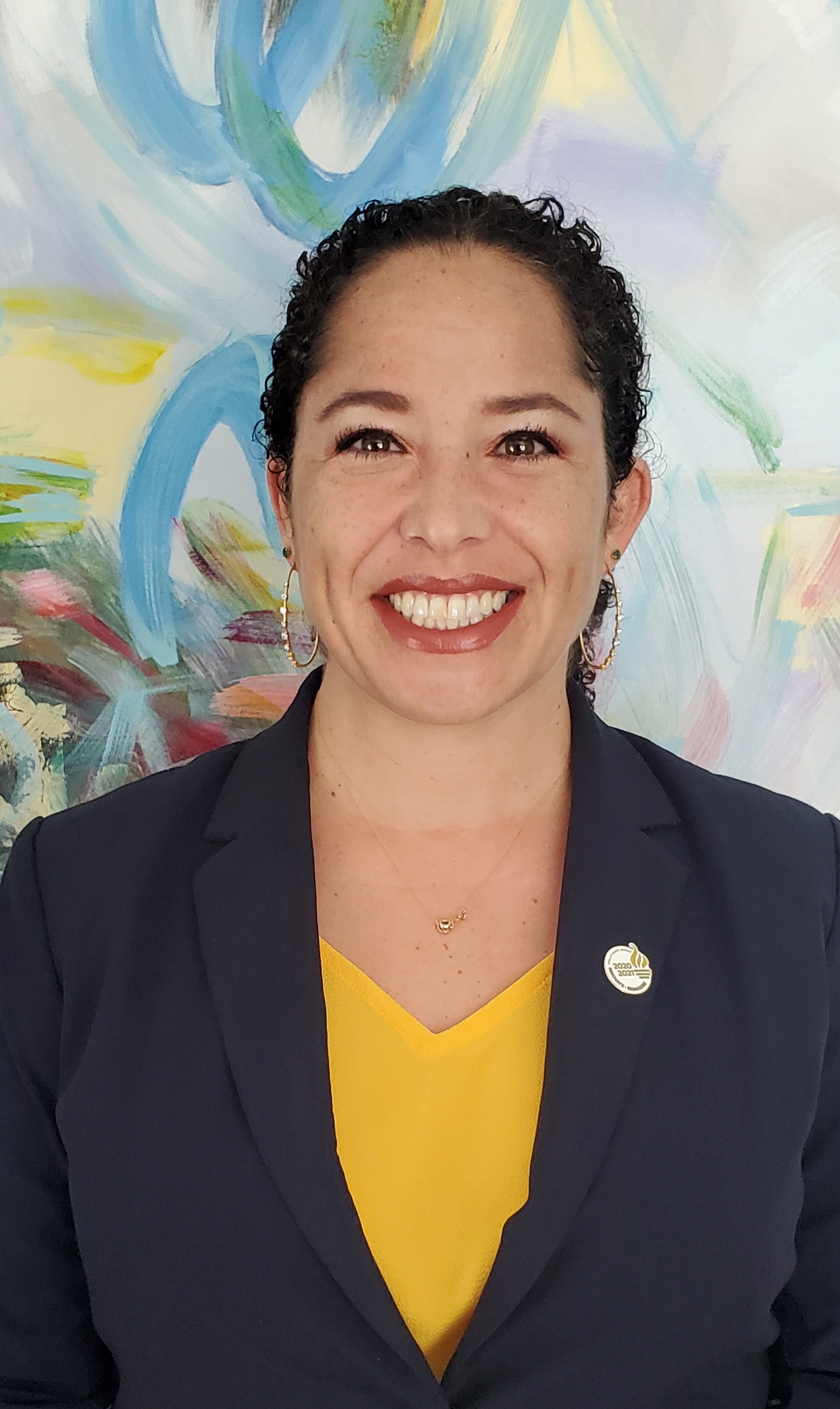 A photo of a woman smiling at a camera with a colorful background.