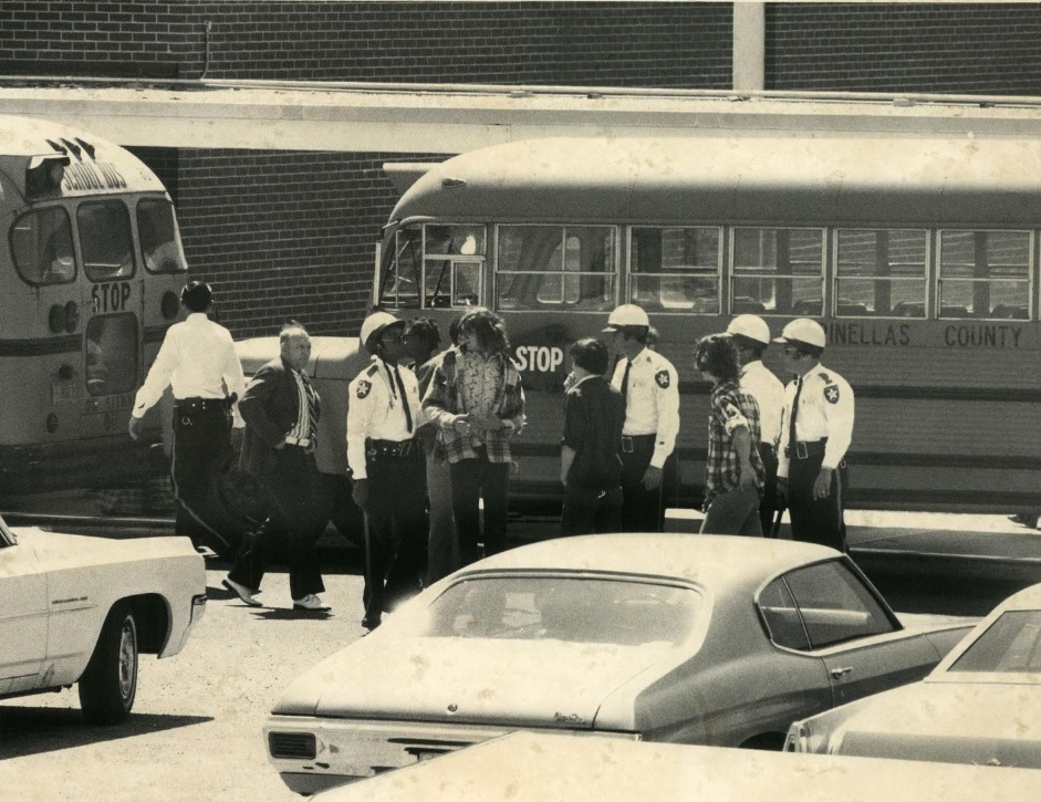 A black and white photo of police officers in uniform with students in a parking lot near a school bus.