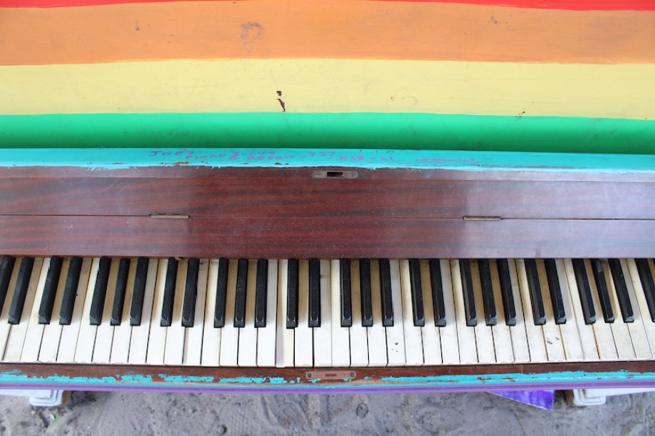 A close up photo of a rainbow painted piano with black and white keys.