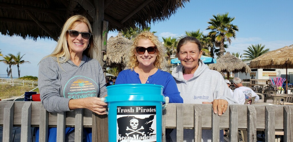 """Three women pose outside on a boardwalk with palm trees in front of a blue bucket with a pirate flag and the words """"Trash Pirates"""" on it."""