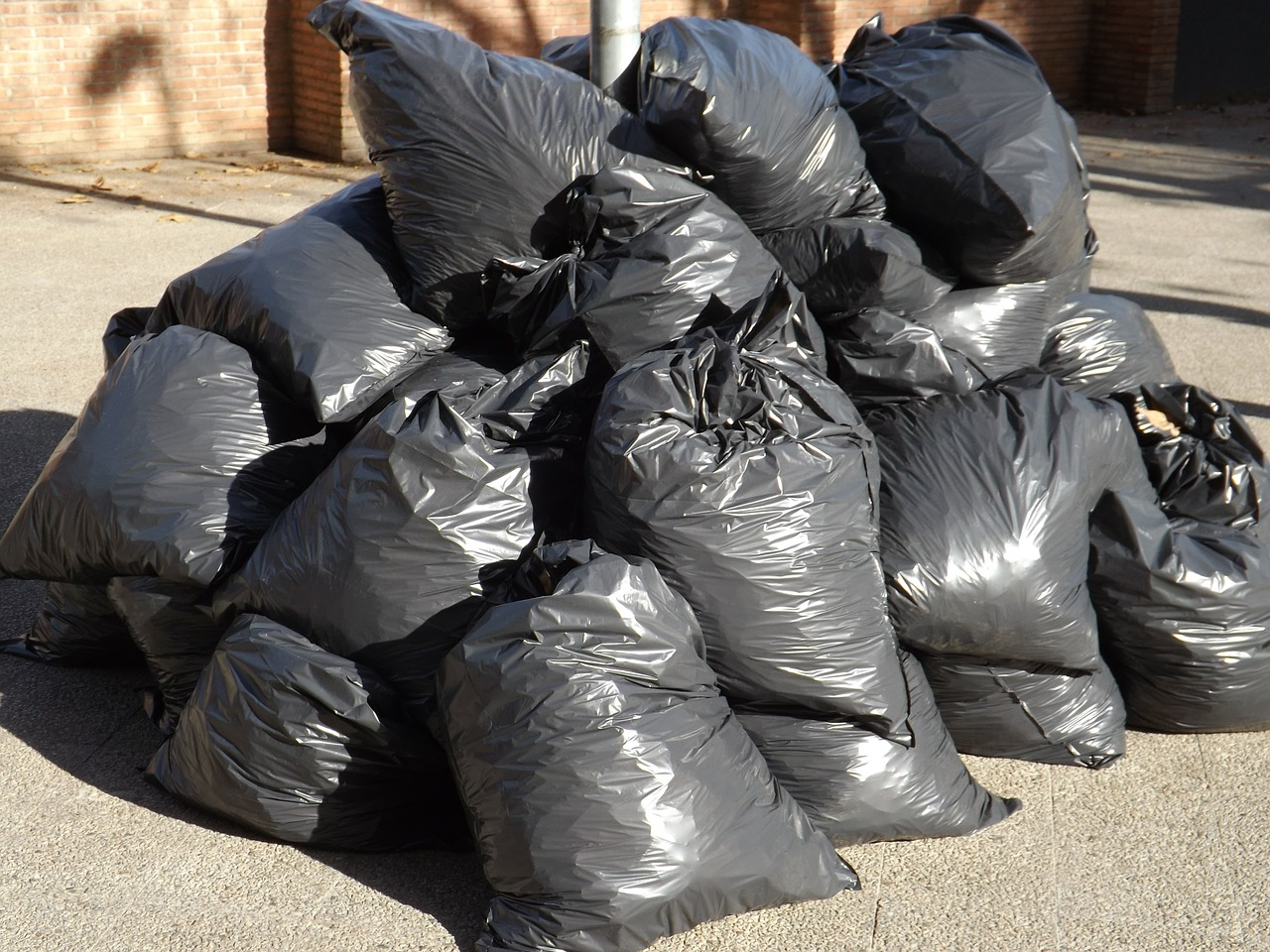 A pile of full, black garbage bags tied up.