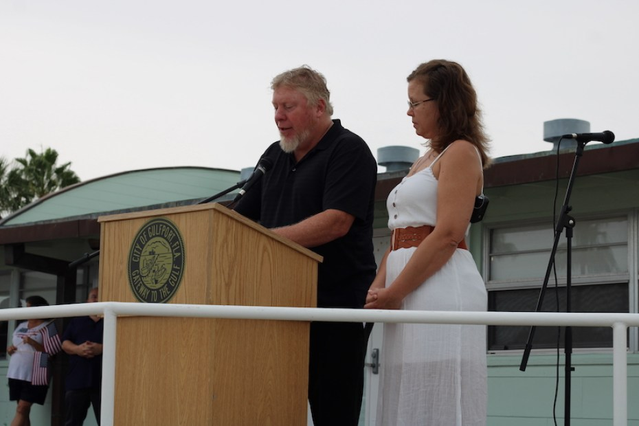 A photo of a men and a woman standing at a podium outside.