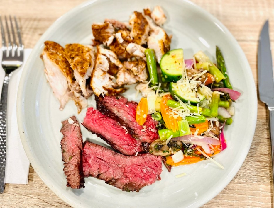 A photo of a white plate of food with steak strips vegetables and fish.