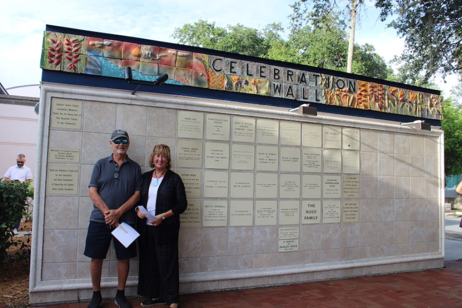 """A photo of a man and a woman leaning against a wall with a colorful top that reads """"Celebration Wall"""""""