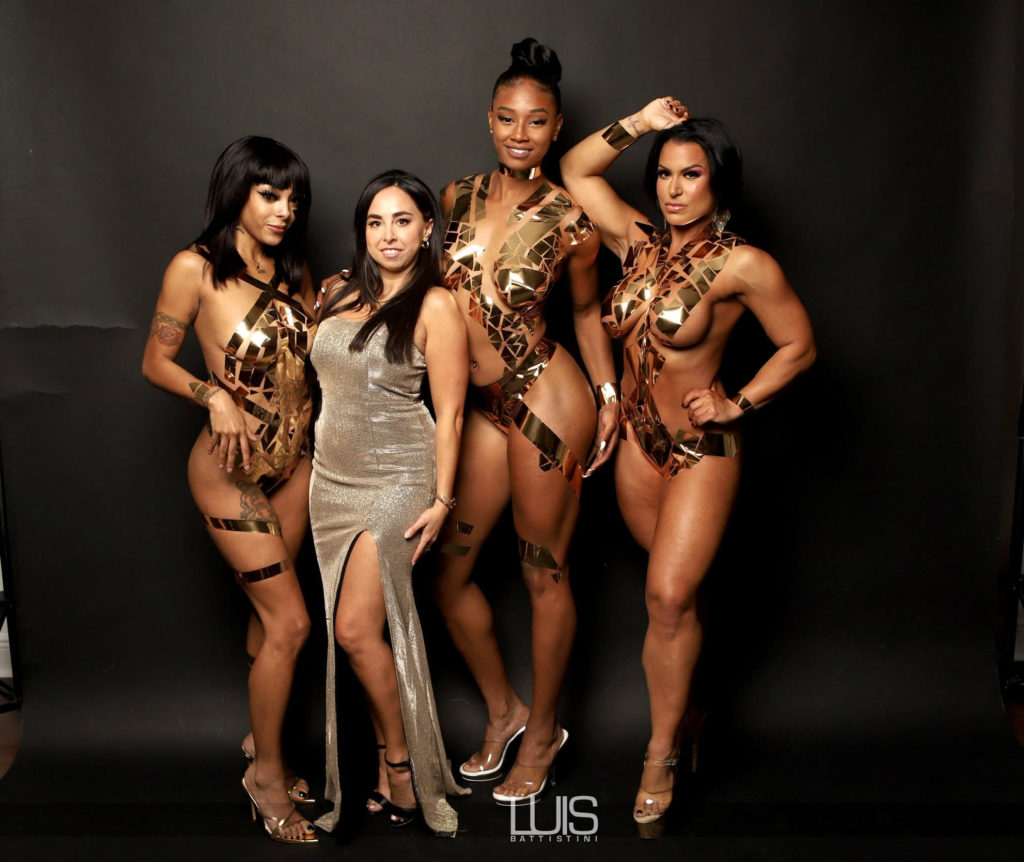 A photo of three women in bikini-style clothes made of electrical tape, with another woman in a gold dress standing with them, posed for a professional photo.