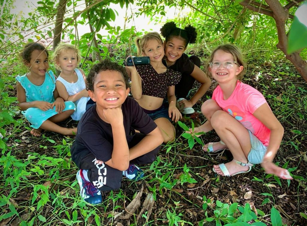 A photo of six young children smiling and kneeling on the ground under a tree.