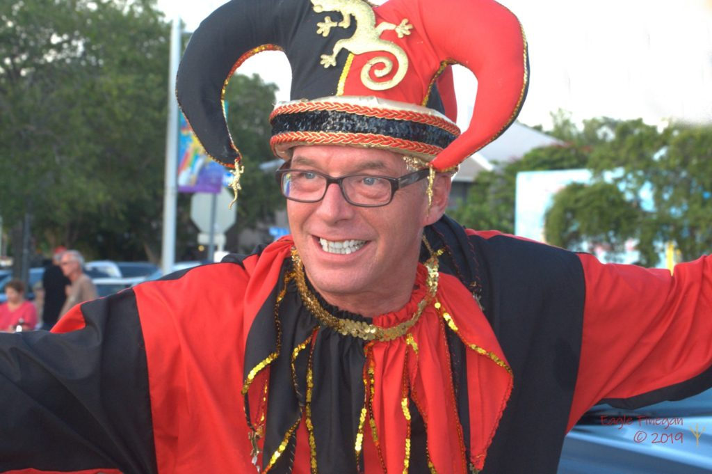 A photo of a man smiling in a red and black jester costume with matching hat.