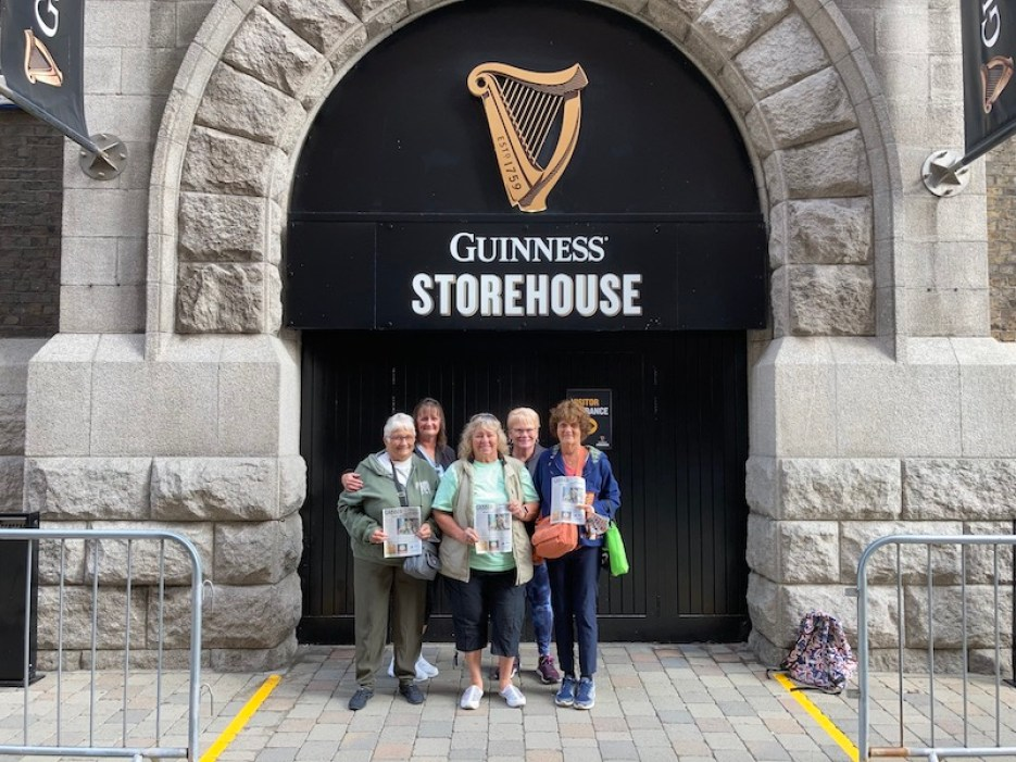 """A photo of a group of people posing in front of a stone building with a large black door that reads """"Guinness Storehouse"""""""