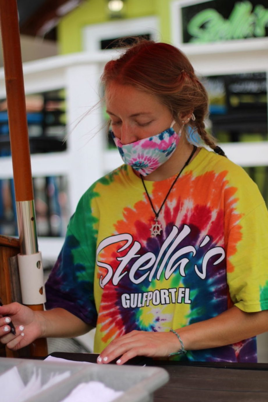"""A young woman in a face mask and a tie-dyed t-shirt with the words """"Stella's Gulfport FL"""" on it."""