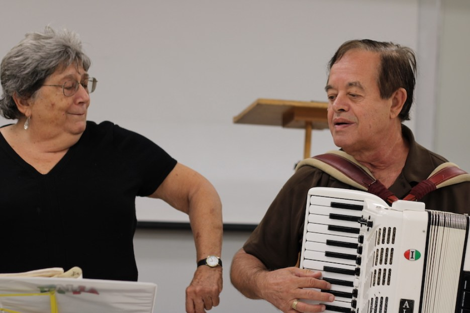 A photo of a woman watching as a man plays a white accordion.
