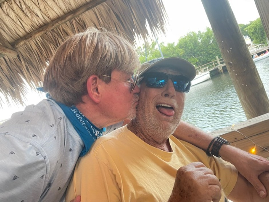 A photo of a person kissing a man in a ballcalp and sunglasses on the cheek with a thatch roof and water in the background.