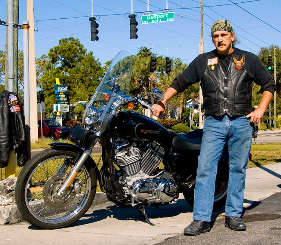 A photo of a man in jeans and a leather vest with a handkerchief on his head, standing next to a large black motorcycle near an intersection.