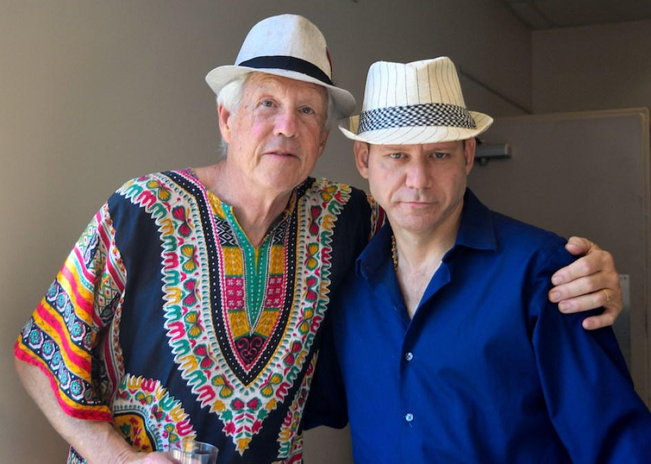 A man in a multicolor shirt and white hat with his arm around a man in a blue shirt and white hat.