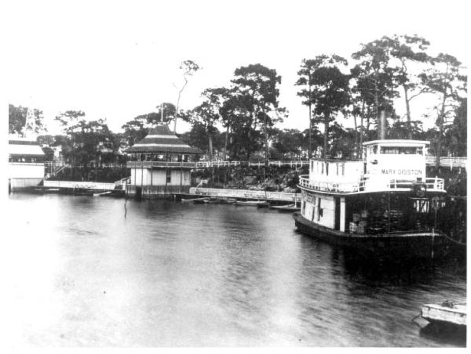 An old black and white photo of boats on the water near a coast.