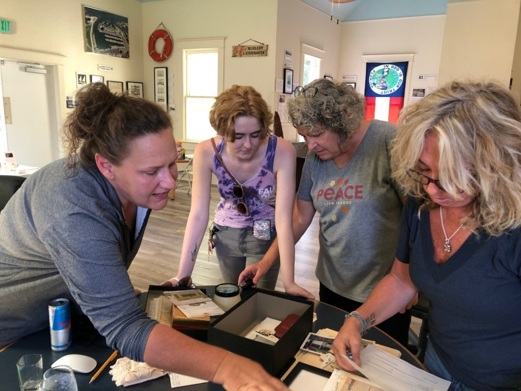 A photo of a group of women in a museum looking over old photos and memorabilia on a table.