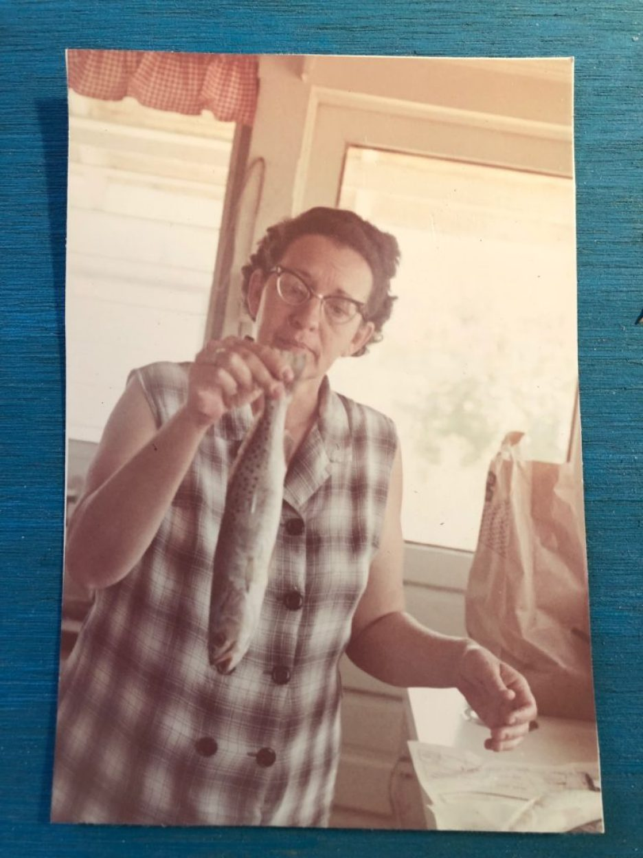 An old color photo of a woman in glasses and a plaid shirt holding up a mullet fish by the tail in a kitchen.