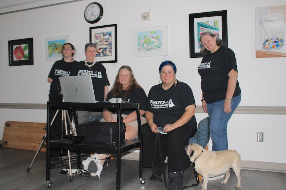 A photo of a group of women in black t-Shirts sitting around a laptop smiling at the camera, with a small brown dog on the floor.