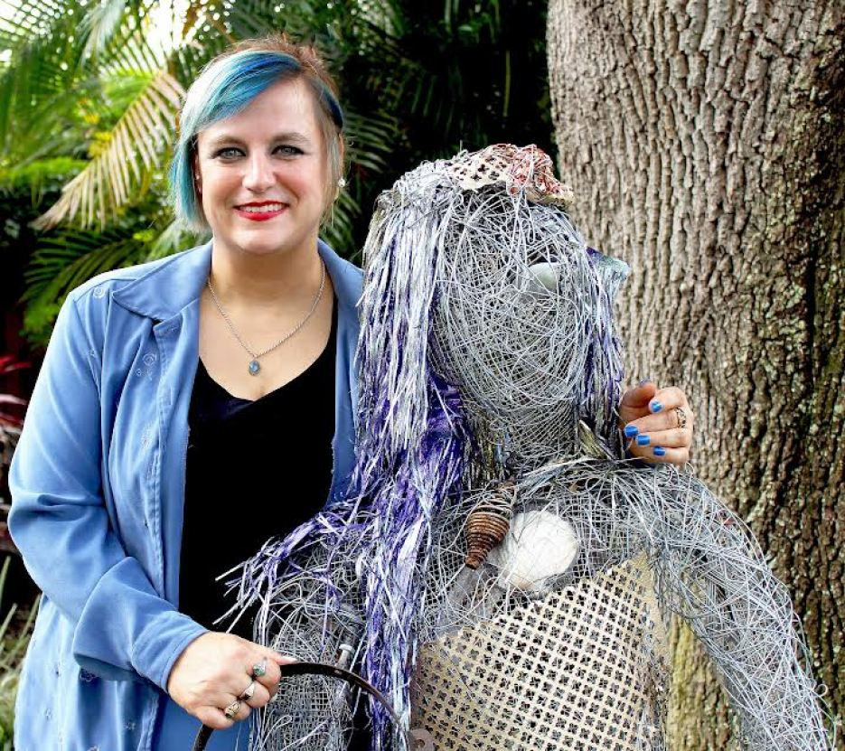 A photo a woman in a blue shirt and black tank top with short blue hair smiling at the camera while standing next to a wire sculpture.