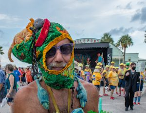 A photo of a man in a lizard headgear with sunglasses standing in front of an outdoor stage,.