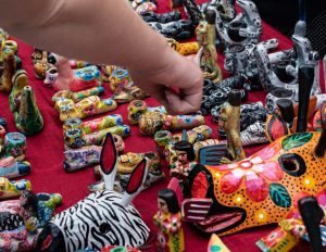 A close-up photo of a table of handmade colorful pipes with a human hand reaching toward them.