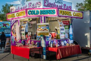 """A photo of a street fair food vendor with colorful signs that read """"Cold Drinks"""" """"Funnel Cakes"""" and """"Elephant Ears"""""""