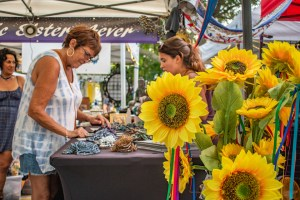 A photo of two women looking at wares on a table in a white outdoor tent with sunflowers in the foreground.