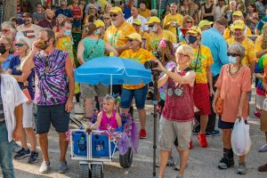 A photo of a small child in a stroller under a blue umbrella in a crowd full of people in colorful shirts.