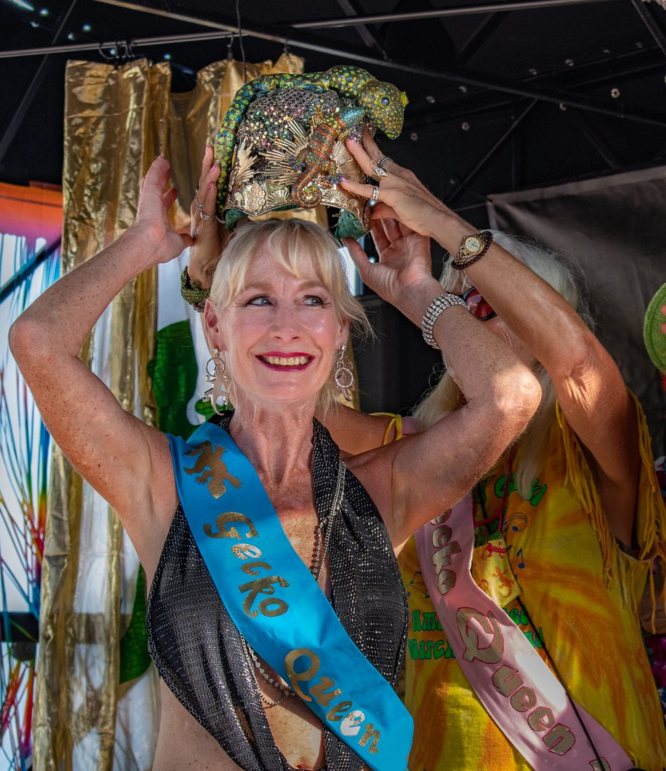 """A photo of a smiling woman lifting a crown over her head wearing a blue sash that reads """"Gecko Queen"""""""
